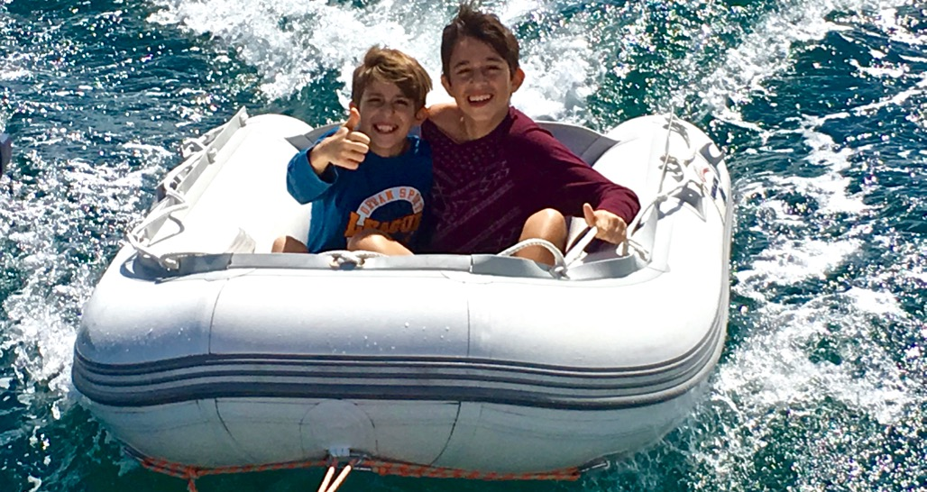 Brothers enjoying a ride behind their private yacht charter