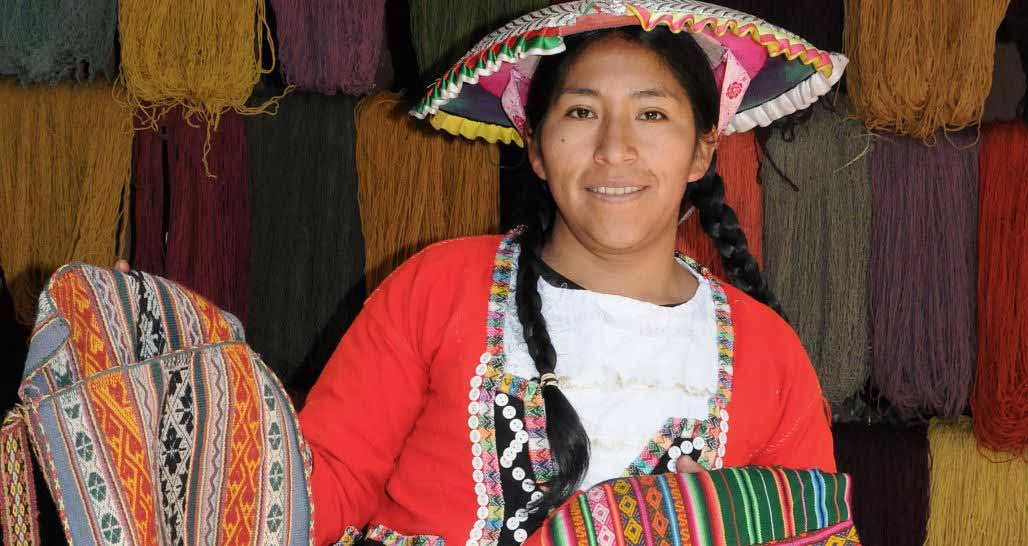 Local girl with hand woven fabrics at Awana Kancha, Sacred Valley